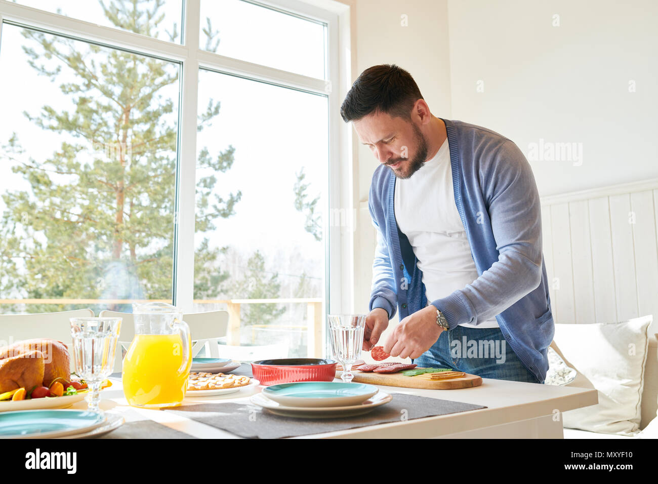 Side view portrait of mature bearded man setting dinner table  while waiting for guests  in sunlit dining room at home, copy space - Stock Image