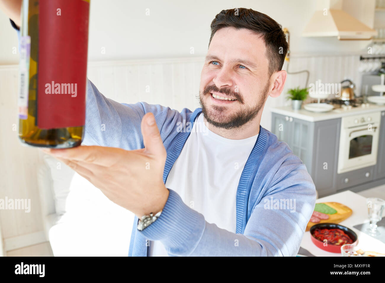 Portrait of smiling bearded man holding wine bottle, inspecting color and quality while setting dinner table  waiting for guests in sunlit dining room - Stock Image