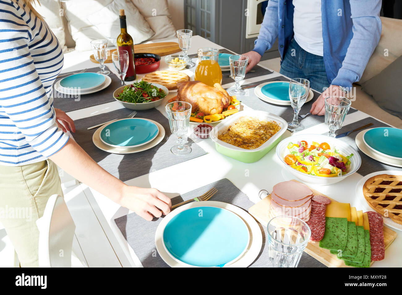 High angle portrait of unrecognizable modern couple setting dinner table  while waiting for guests  in sunlit dining room at home, focus on delicious  - Stock Image