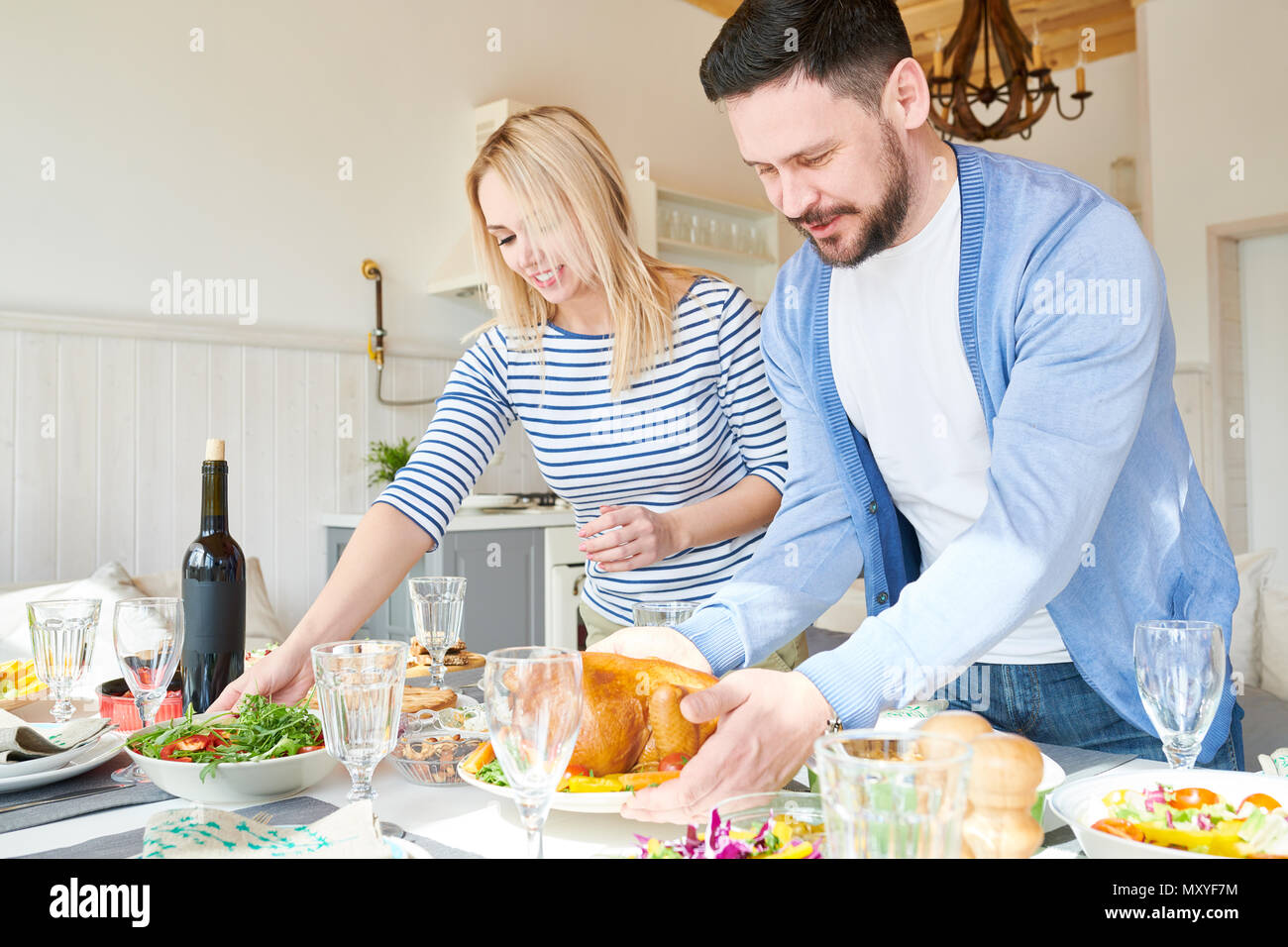Portrait of modern young couple setting dinner table  while waiting for guests  in sunlit dining room at home, focus on mature bearded in foreground - Stock Image