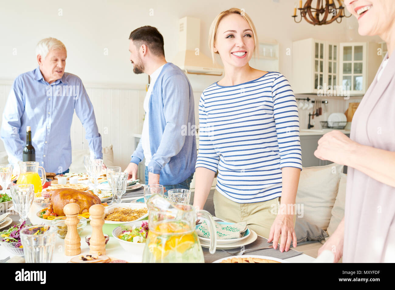 Portrait of happy two generation family preparing dinner together serving table with delicious homemade dishes for holiday party  in modern sunlit apa - Stock Image