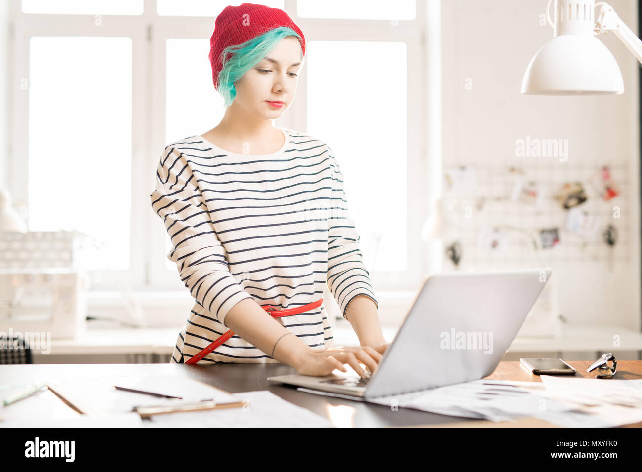 Waist up portrait of contemporary young woman  with green hair using laptop while working on creative fashion design  project in small atelier studio - Stock Image
