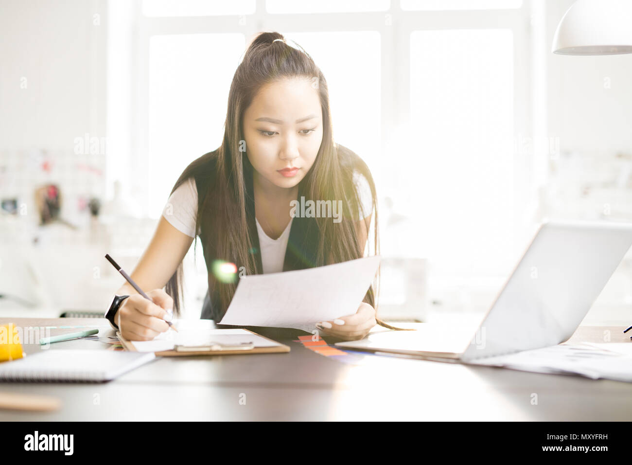 Portrait of focused creative Asian woman drawing sketches for while standing at work table in sunlit fashion design atelier, lens flare - Stock Image