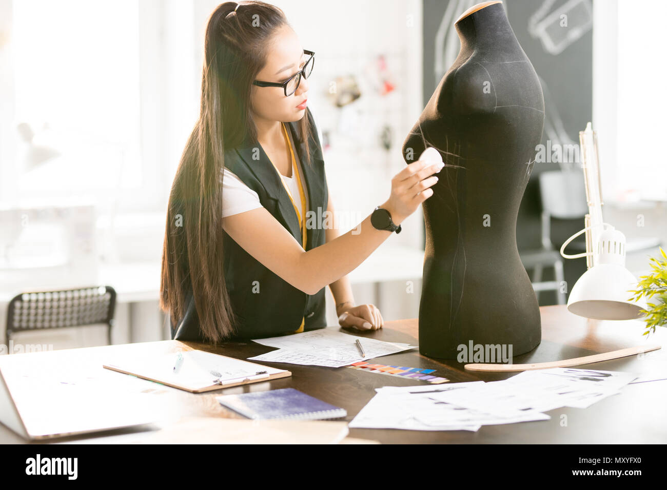 Waist up portrait of focused Asian woman working in fashion design tracing sewing dummy standing at tailors table in sunlit modern atelier studio - Stock Image