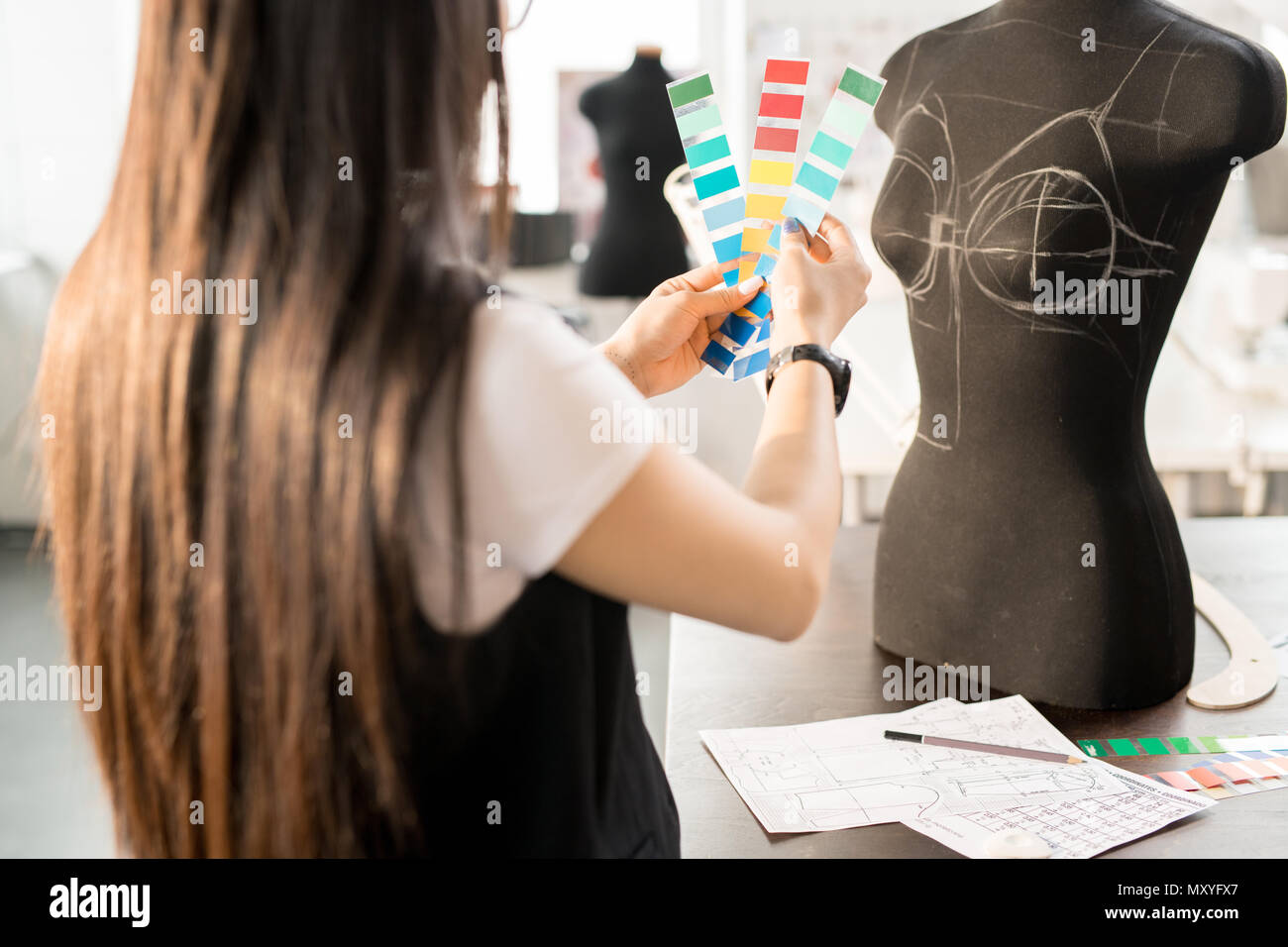 Back view portrait of focused Asian woman working in fashion design choosing color palette holding swatches standing at table by sewing dummy in moder - Stock Image