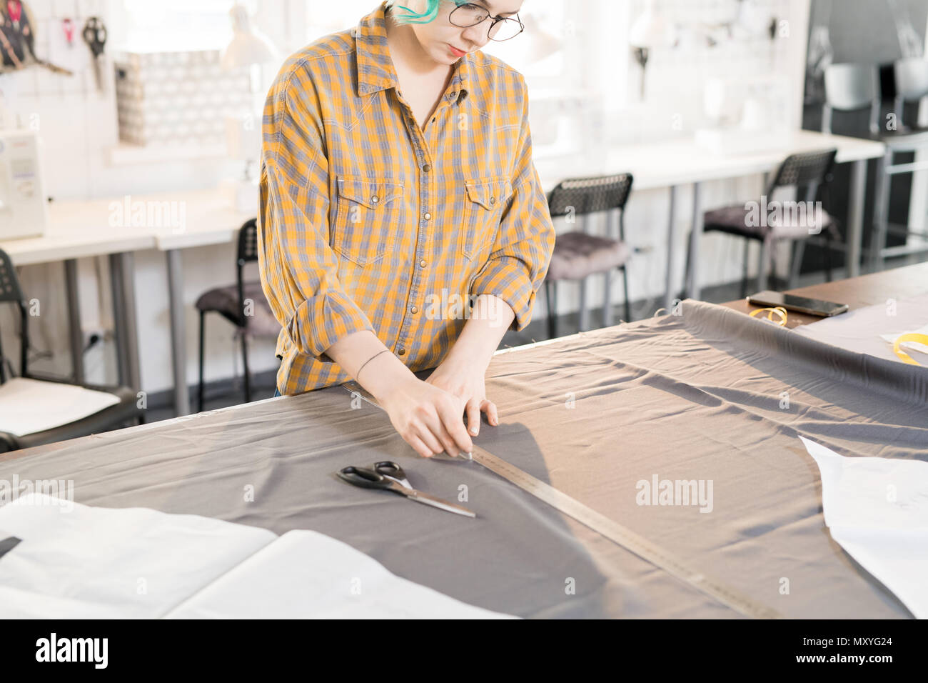Portrait of  female tailor tracing fabric with white chalk while sewing custom made clothes, copy space - Stock Image