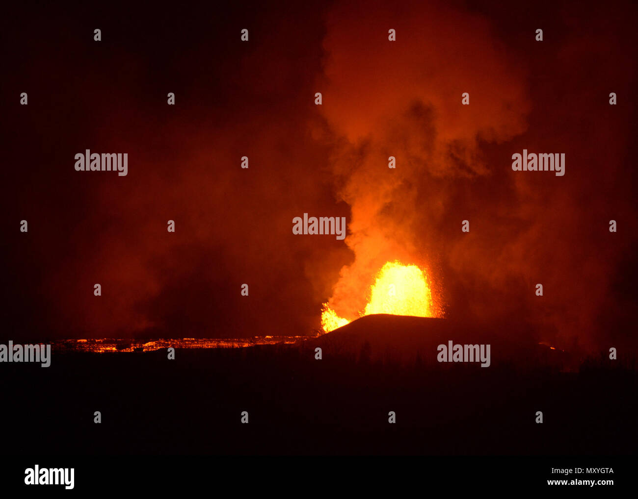 Lava erupts from a fissure in the Kilauea region near Hilo, Hawaii, during a night survey flight by UH-60 helicopter crews from the 25th Combat Aviation Brigade on June 2, 2018. The aircraft are part of an active-duty military force augmenting the Hawaii National Guard's Joint Task Force 5-0. Joint Task Force 5-0 is the military organization providing support to state and local disaster response efforts to the on-going eruptions. (Air National Guard photo by Lt. Col. Wayde Minami) - Stock Image