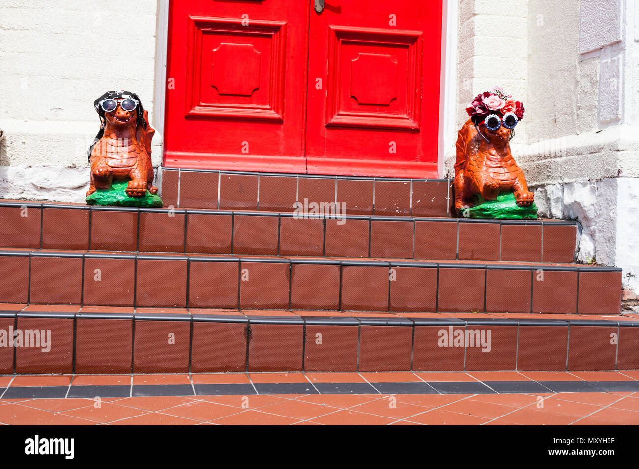 House Entrance With Red Door And Two Dragon Statues On The Floor