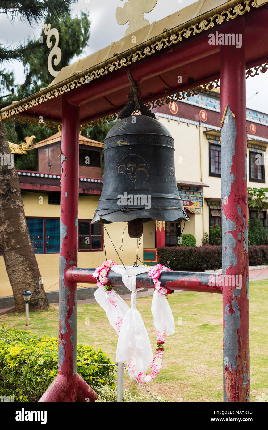 Namdrolling Monastery ornate bell with letters engraved on it at entrance in Coorg Karnataka - Stock Image
