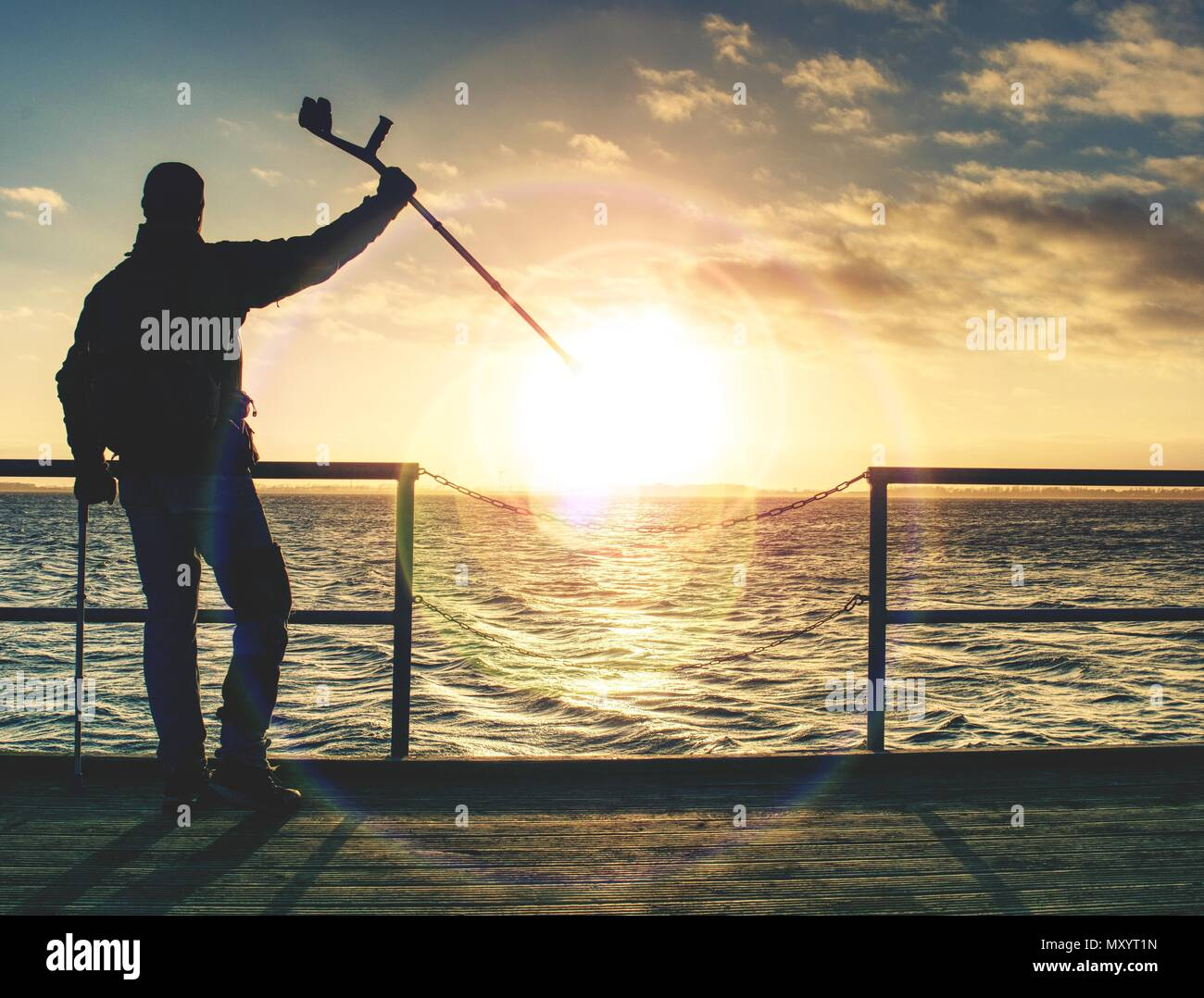 Man with a crutches on mole pier. Tourist with broken leg on crutches. Traveler with hurt leg in bandages. Full length of man with broken leg. - Stock Image