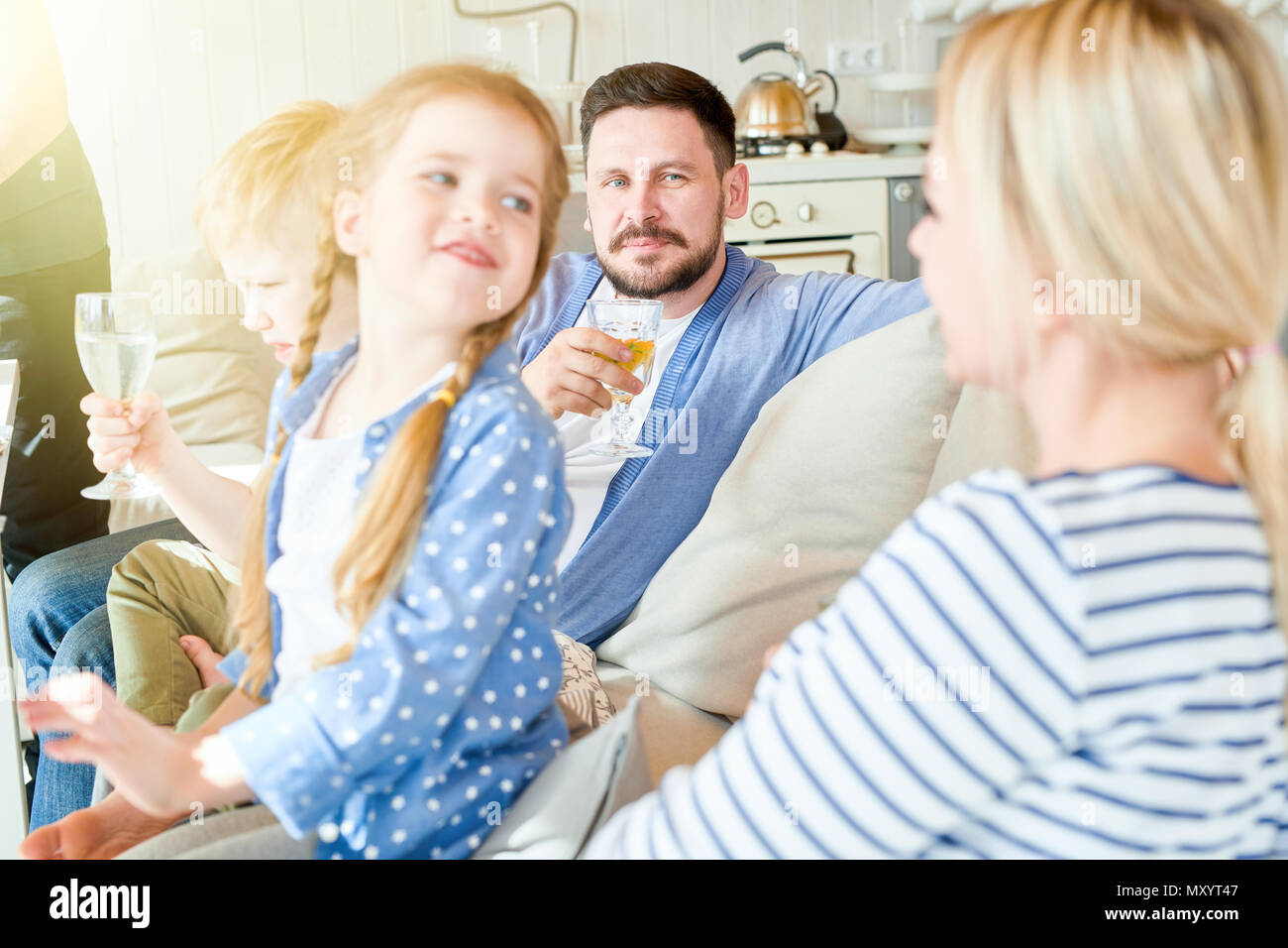 Portrait of happy family with two kids sitting on couch enjoying festive dinner party at home, focus on cute red haired girl turning to look at her mo - Stock Image