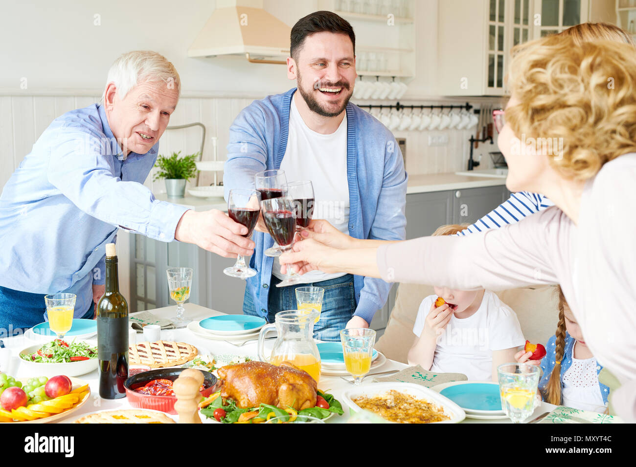 Portrait of happy two generation  family enjoying dinner together clinking glasses and toasting standing at festive table during  holiday  celebration - Stock Image