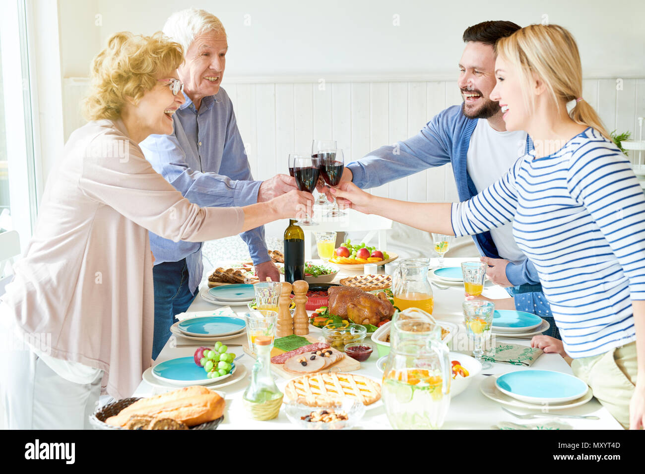 Side view portrait of happy two generation family enjoying dinner together clinking glasses at festive table with delicious dishes and smiling during  - Stock Image