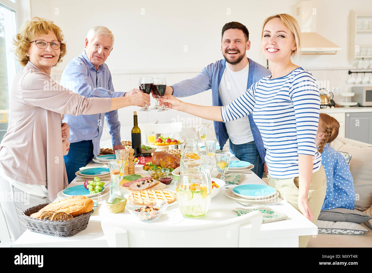 Portrait of happy two generation  family enjoying dinner together clinking glasses over festive table  with delicious dishes and smiling looking at ca - Stock Image
