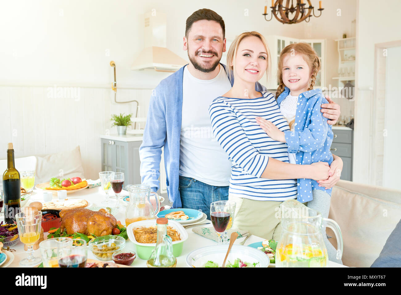 Portrait of happy young family  with cute little girl standing at festive dinner table with delicious dishes and smiling at camera in modern apartment - Stock Image