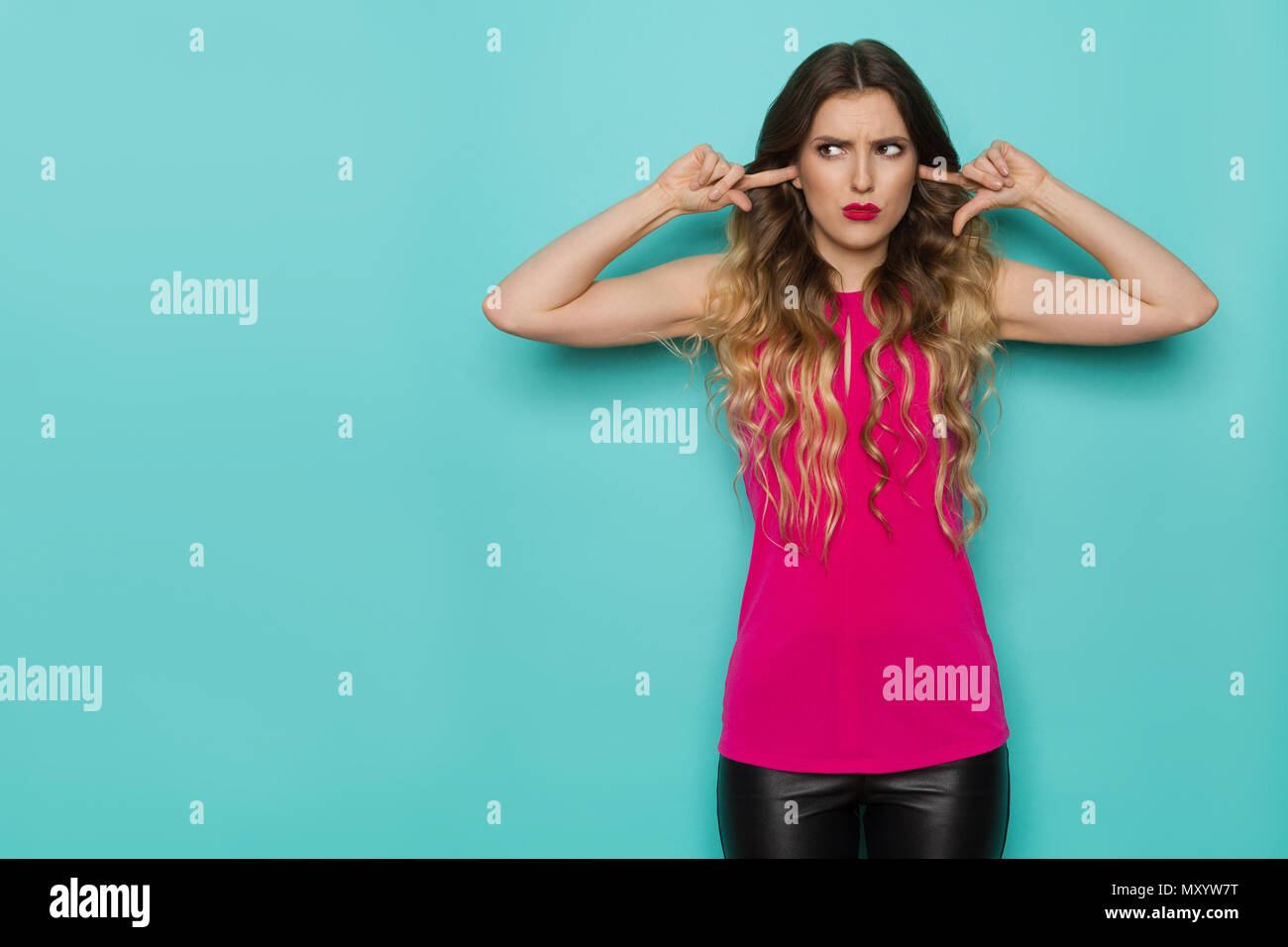 Beautiful grimacing young woman in pink top closes her ears with fingers and looks away. Three quarter length studio shot on turquoise background. - Stock Image