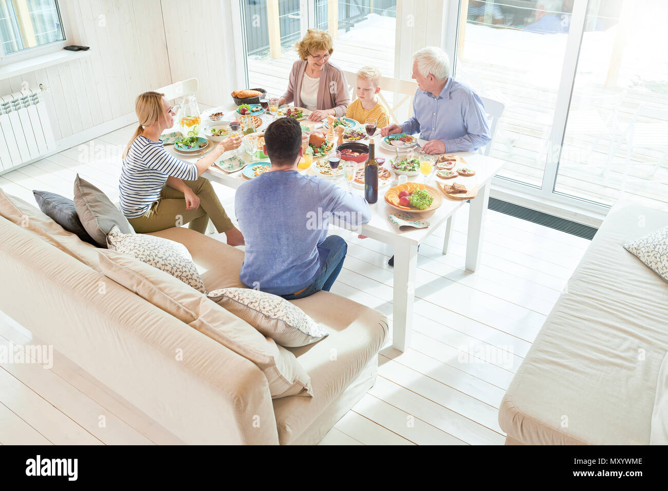 Wide angle portrait of happy two generation  family enjoying dinner together sitting at festive table with delicious dishes during  holiday  celebrati - Stock Image