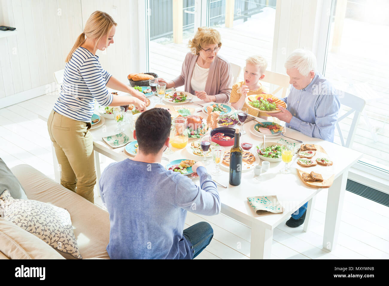 Portrait of happy two generation  family enjoying dinner together sitting at festive table with delicious dishes during  holiday  celebration in sunli - Stock Image