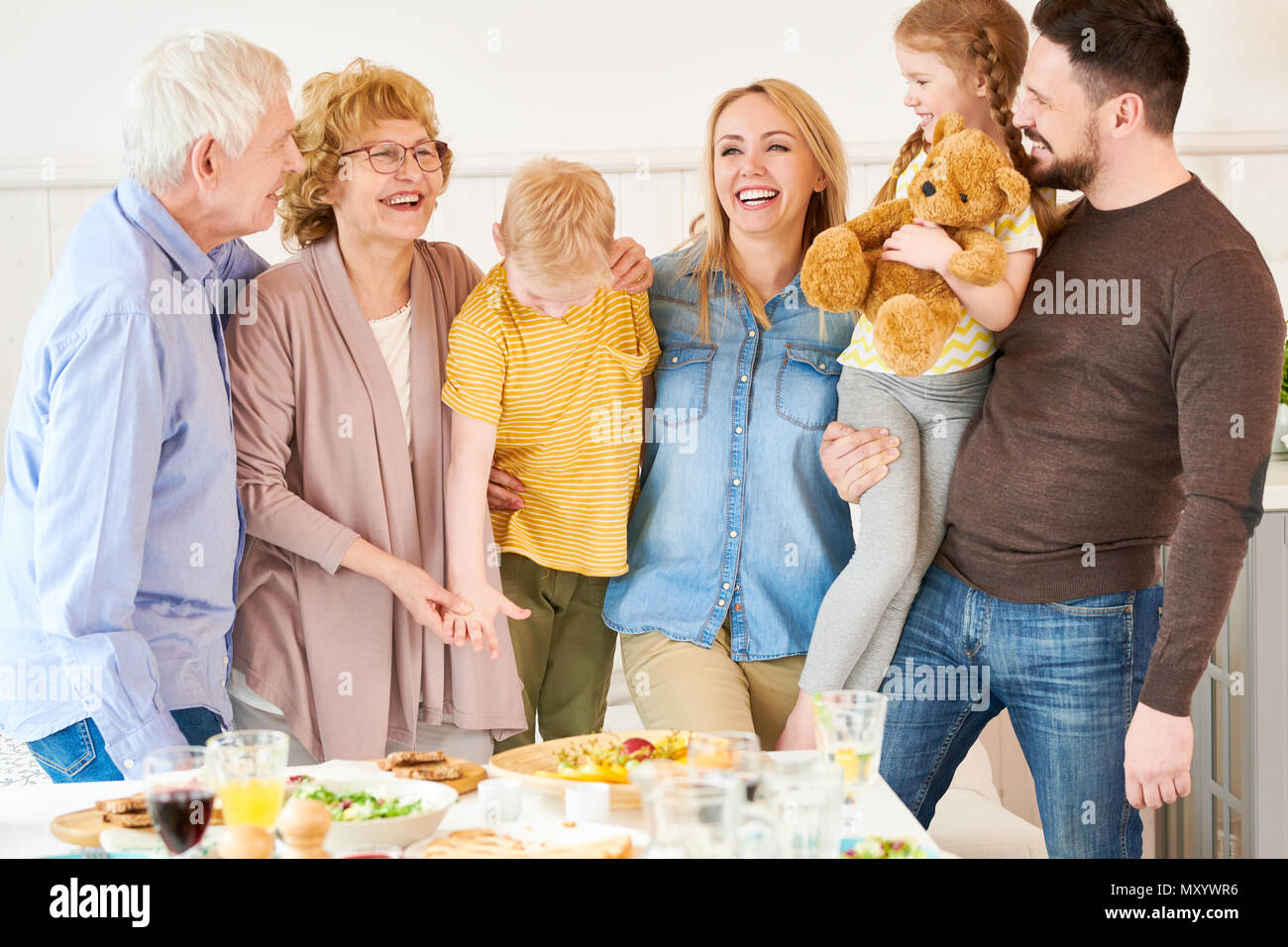 Portrait of carefree two generation family of six posing  at home and smiling happily while  standing at festive dinner table - Stock Image