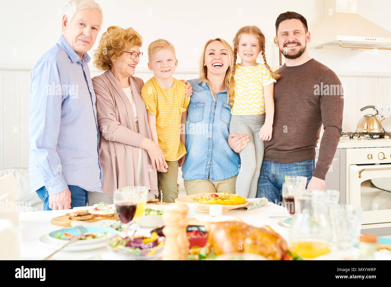 Portrait of carefree two generation family of six posing  at home and smiling   standing at festive dinner table - Stock Image