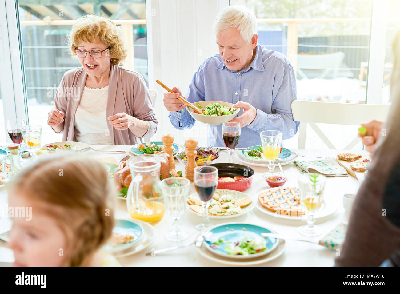Portrait of happy family enjoying dinner together sitting round festive table with delicious dishes, focus two grandparents, copy space - Stock Image