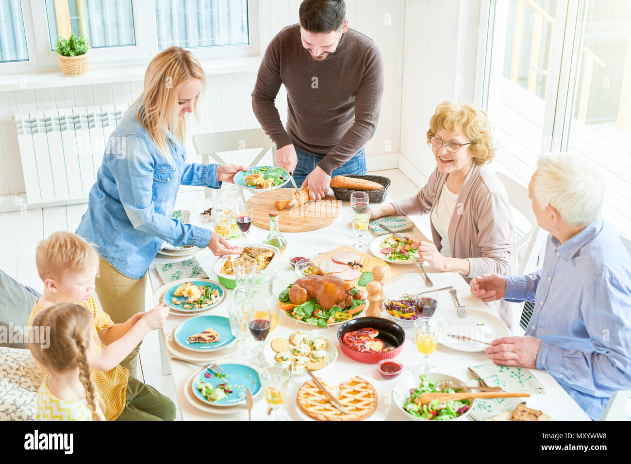 High angle portrait of big happy family enjoying dinner together sitting round festive table with delicious dishes,  young woman serving food during   - Stock Image