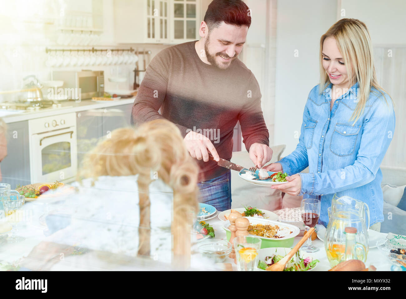 Portrait of happy couple serving food while enjoying family dinner at home in sunlight - Stock Image