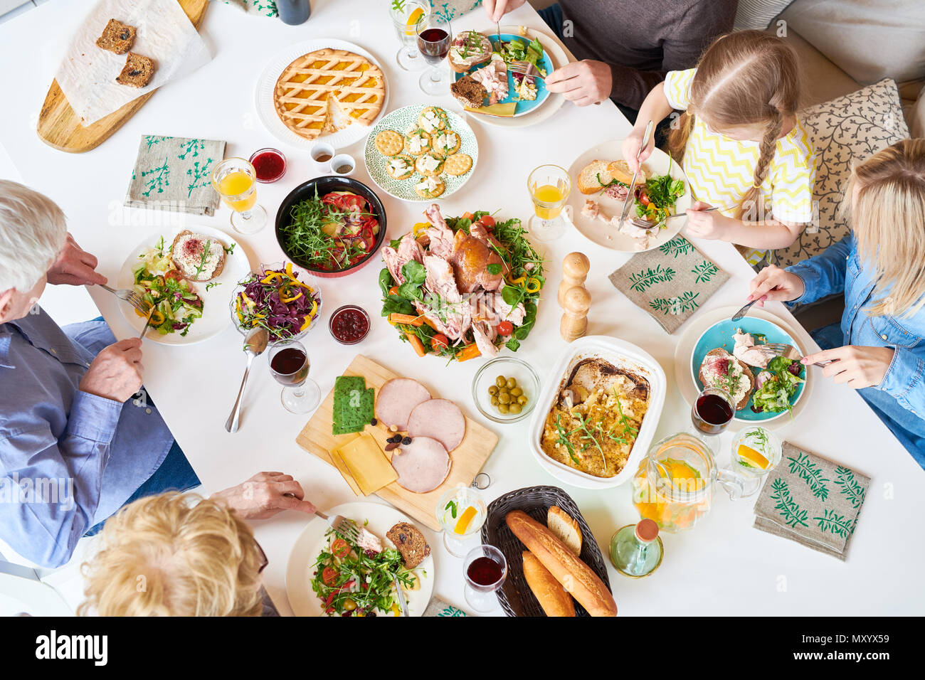 Directly above view of big happy family sitting at dinner table enjoying delicious homemade food during celebration - Stock Image