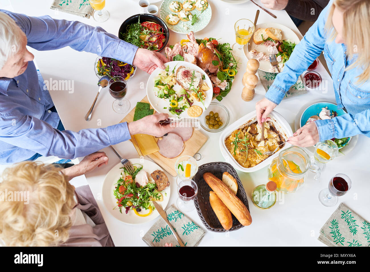 Top view of big happy family sitting at dinner table enjoying delicious homemade food during festive celebration and handing plates across table - Stock Image