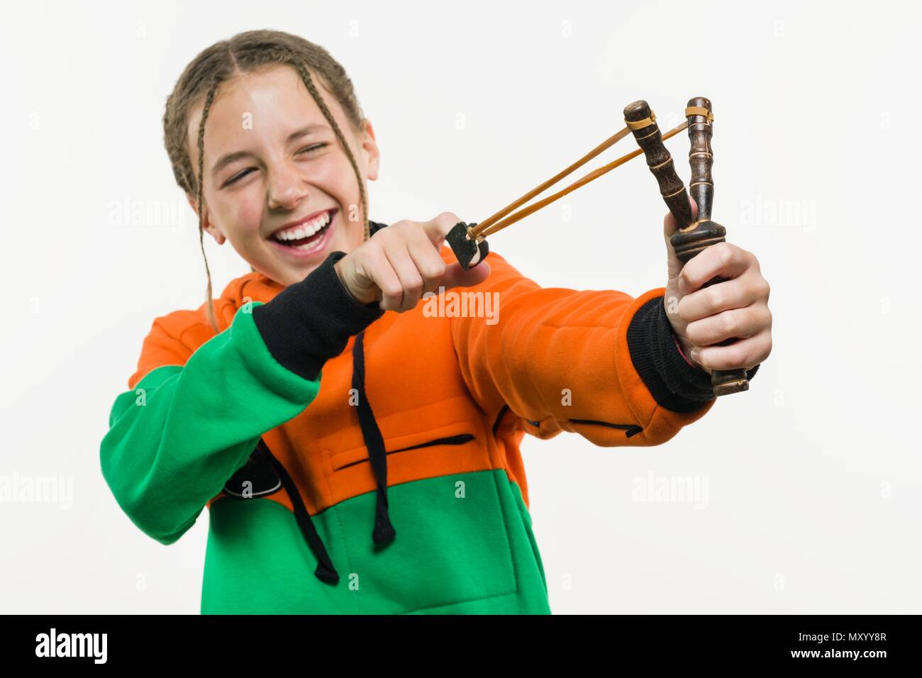 Naughty girl teenager with curly hair holds a slingshot. White Background Studio Stock Photo