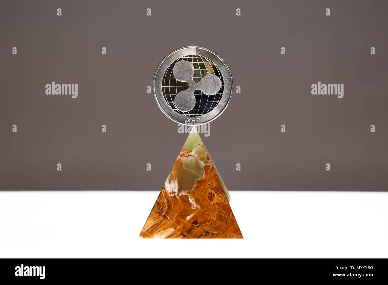 Ripple Coin sitting a top a translucent Onyx Stone. Stone symbolizes, personal power, change, facing fears.  All things people who trade crypro face Stock Photo
