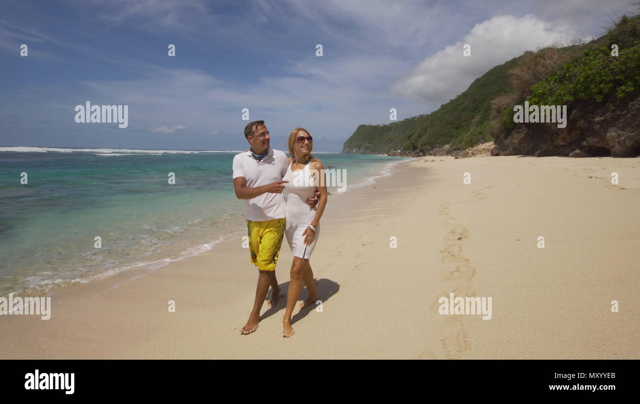 Beautiful Couple embracing walking along the beach. Relationships, Beach, couple on romantic travel honeymoon vacation summer holidays romance. Young happy lovers. Travel concept. Bali. - Stock Image