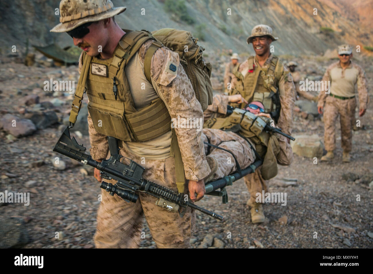 ARTA BEACH, DJIBOUTI (Dec. 12, 2016) U.S. Navy Seaman Marcus Salceda and Petty Officer 3rd Class Charles Niles, hospital corpsmen with Battalion Landing Team 1st Bn., 4th Marines, 11th Marine Expeditionary Unit (MEU), carry a role-playing patient via litter to a casualty collection point while conducting tourniquet drills during Exercise Alligator Dagger, Dec. 12. Secondary medical assessments are conducted on injured personal at casualty collection points: splinting closed fractures, bandaging lacerations, or applying tourniquets to open hemorrhages.   The unilateral exercise provides an oppo - Stock Image