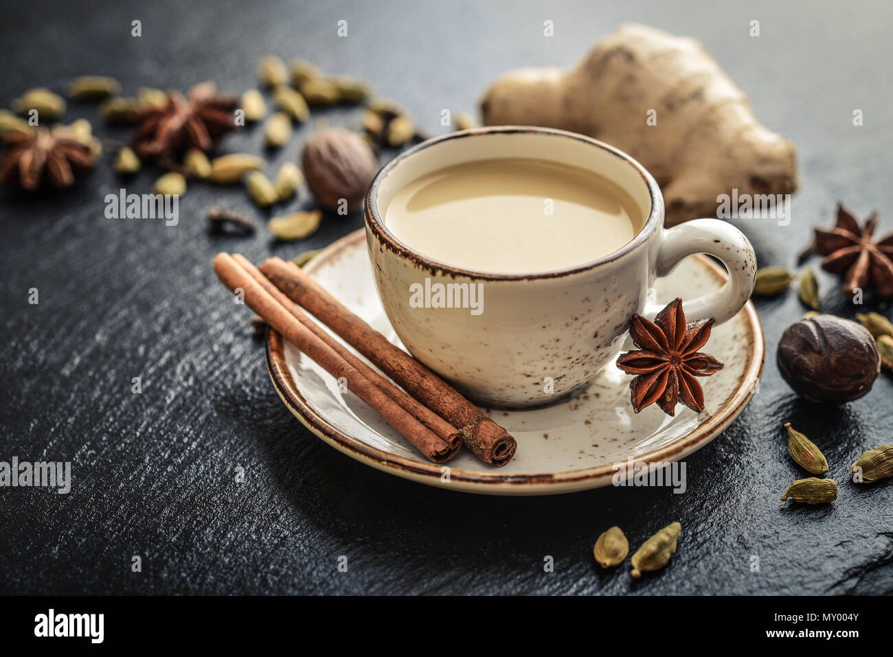 Traditional indian drink - masala tea with spices on black stone  background - Stock Image