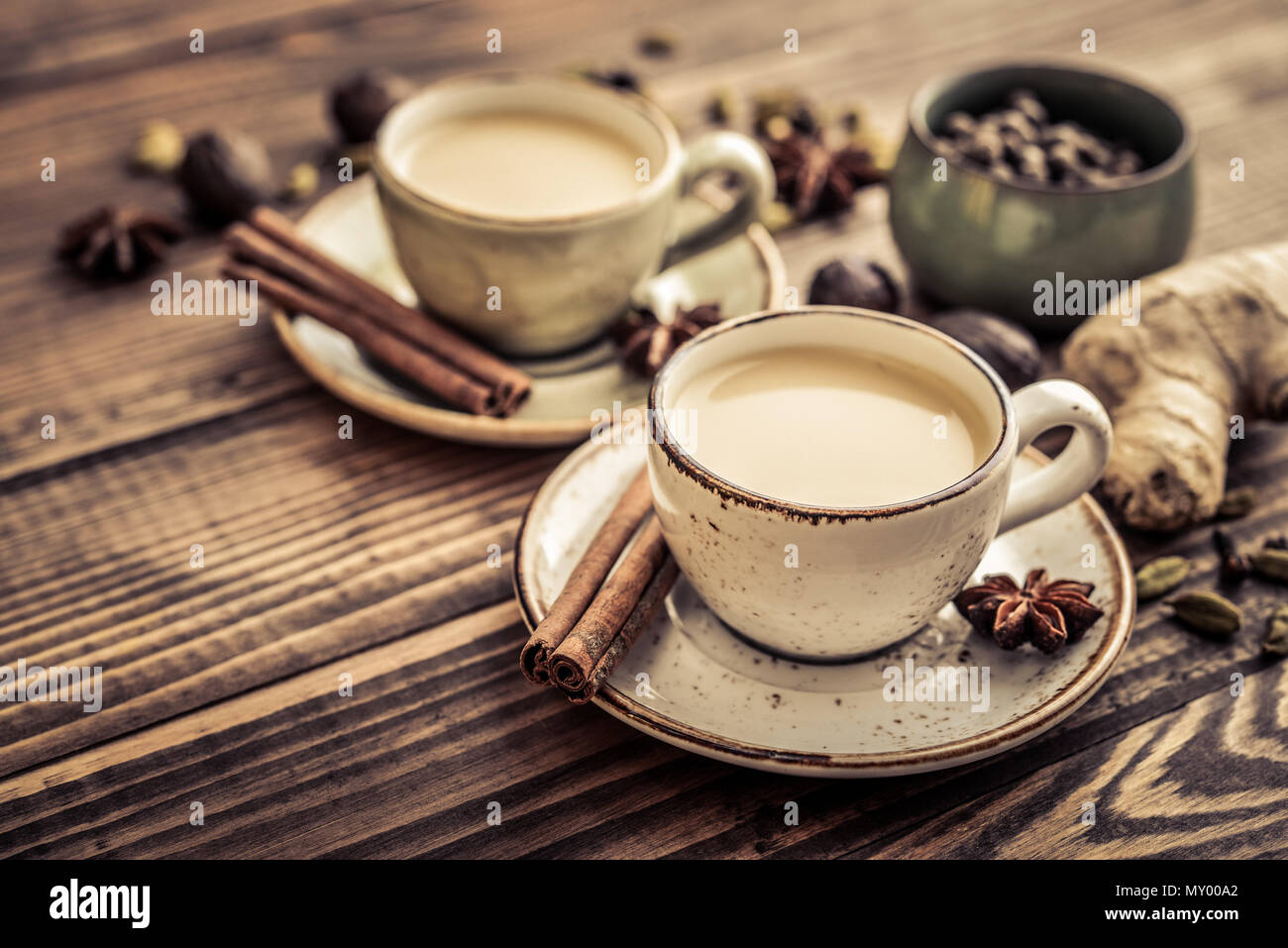 Traditional indian drink - masala chai tea (milk tea) with spices on wooden background Stock Photo