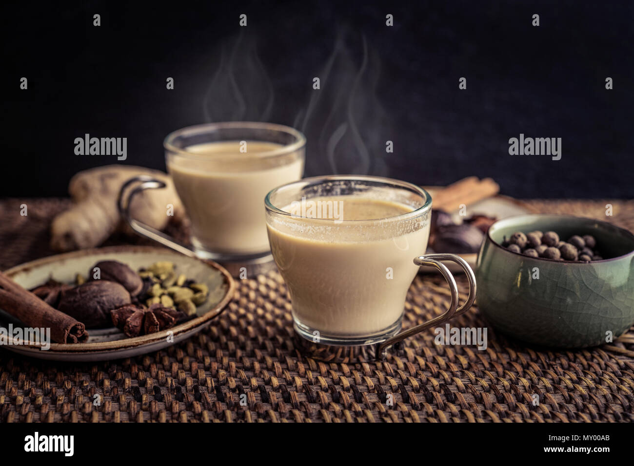 Traditional indian drink - masala chai tea (milk tea) with spices on rattan tray - Stock Photo