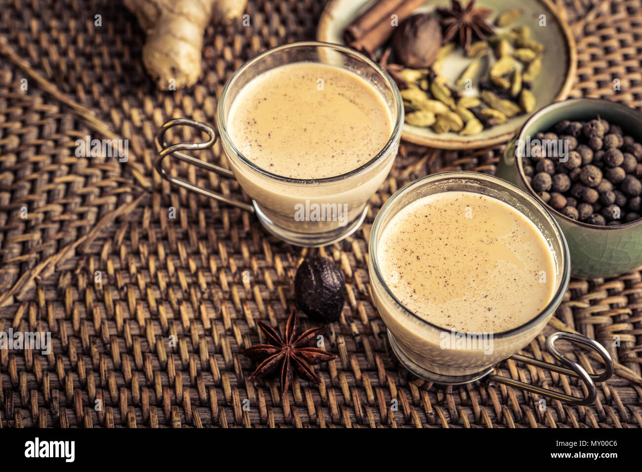Traditional indian grink - masala chai tea (milk tea) with spices on wooden background Stock Photo