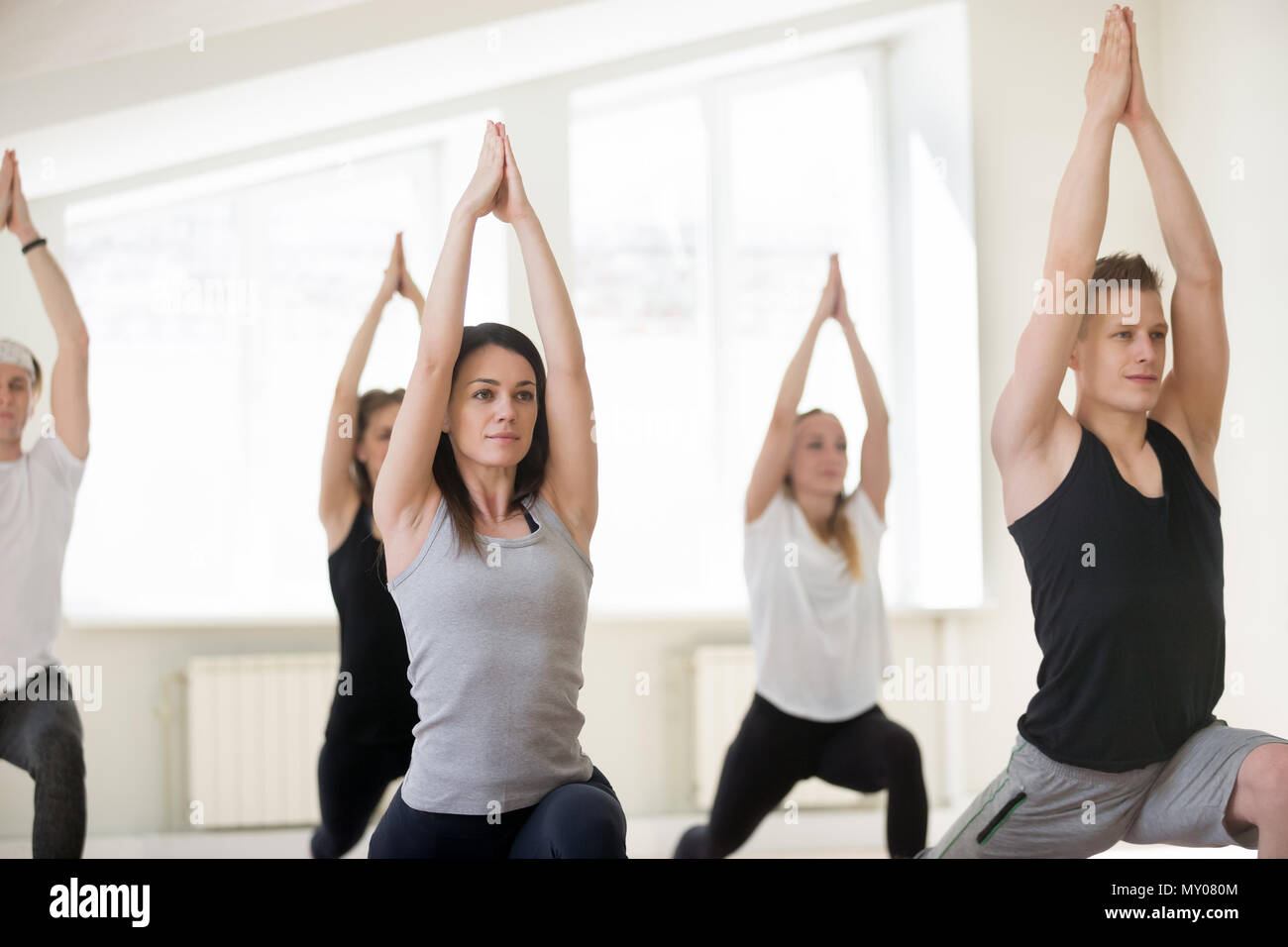 Group of young sporty people practicing yoga lesson, doing Warrior one exercise, Virabhadrasana 1 pose, working out, indoor session, students training Stock Photo
