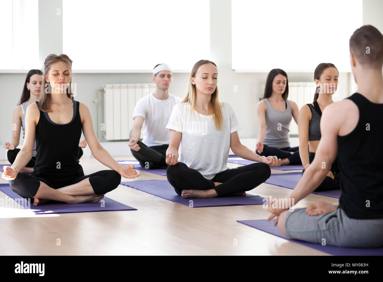 Group Of Young Sporty People Practicing Yoga Lesson With Male Instructor Doing Easy Seat Exercise Sukhasana Pose Working Out Indoor Session Stude