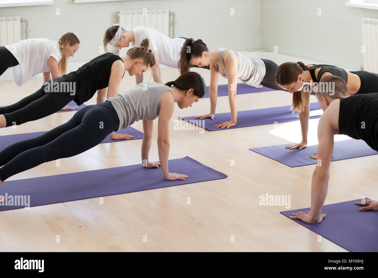 Group of young sporty people practicing yoga lesson, doing Plank exercise, Push ups or press ups pose, working out, indoor full length, students train - Stock Image