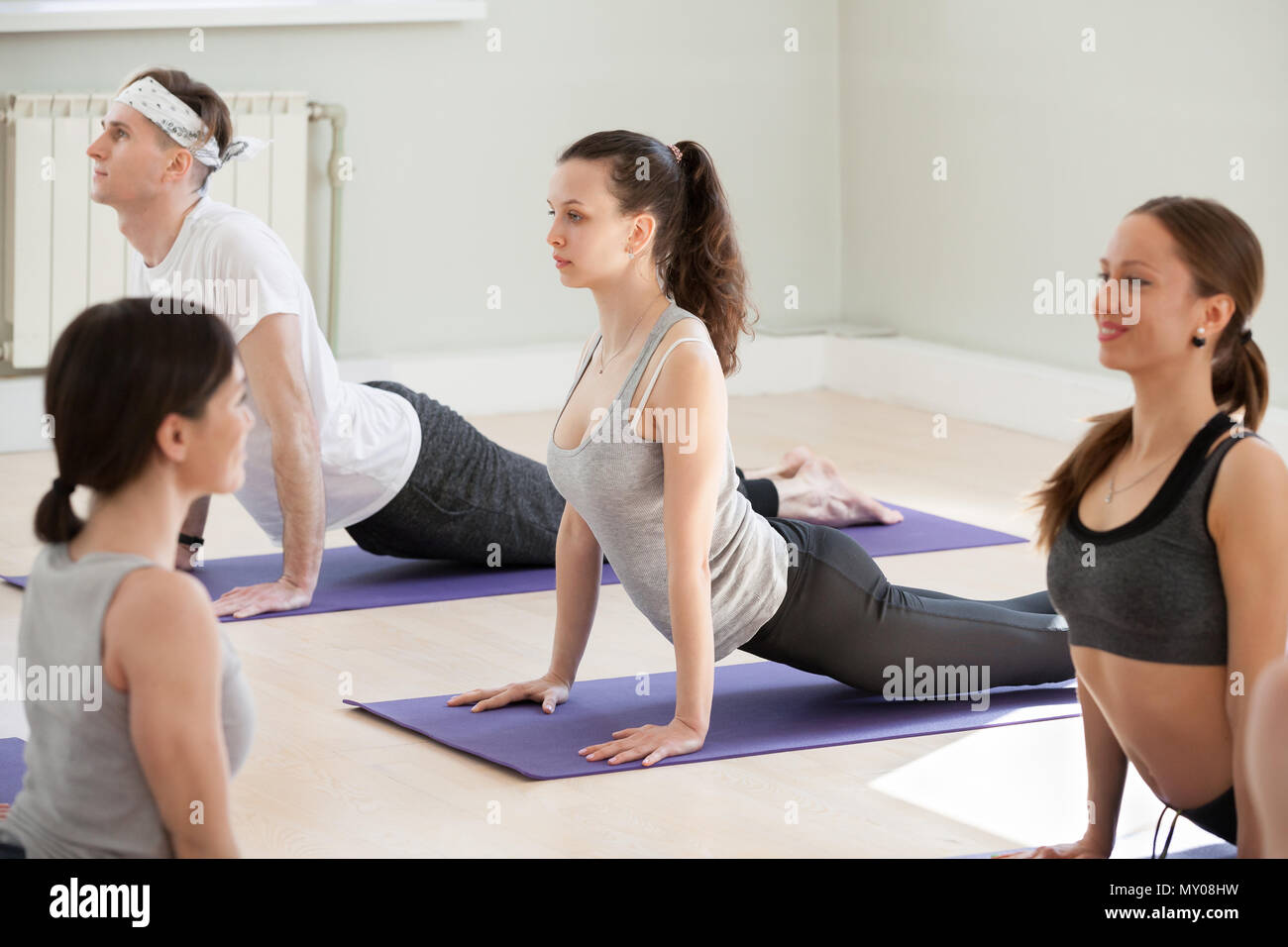 Group of young sporty people practicing yoga lesson, doing upward facing dog exercise, Urdhva mukha shvanasana pose, working out, indoor close up, stu Stock Photo