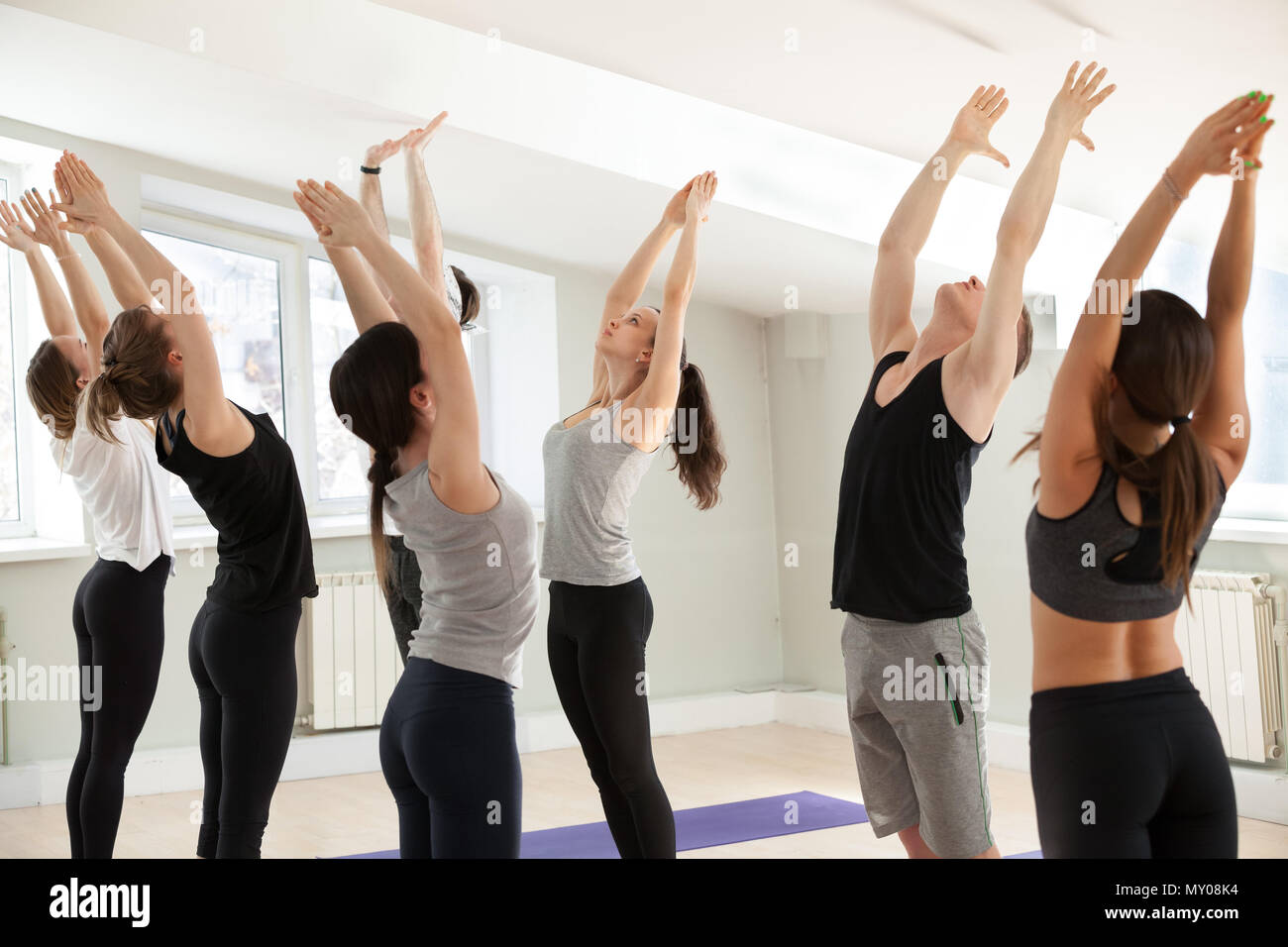 Group of young sporty people practicing yoga lesson, doing Tadasana exercise, mountain pose, working out, indoor close up, yogi students training in s Stock Photo
