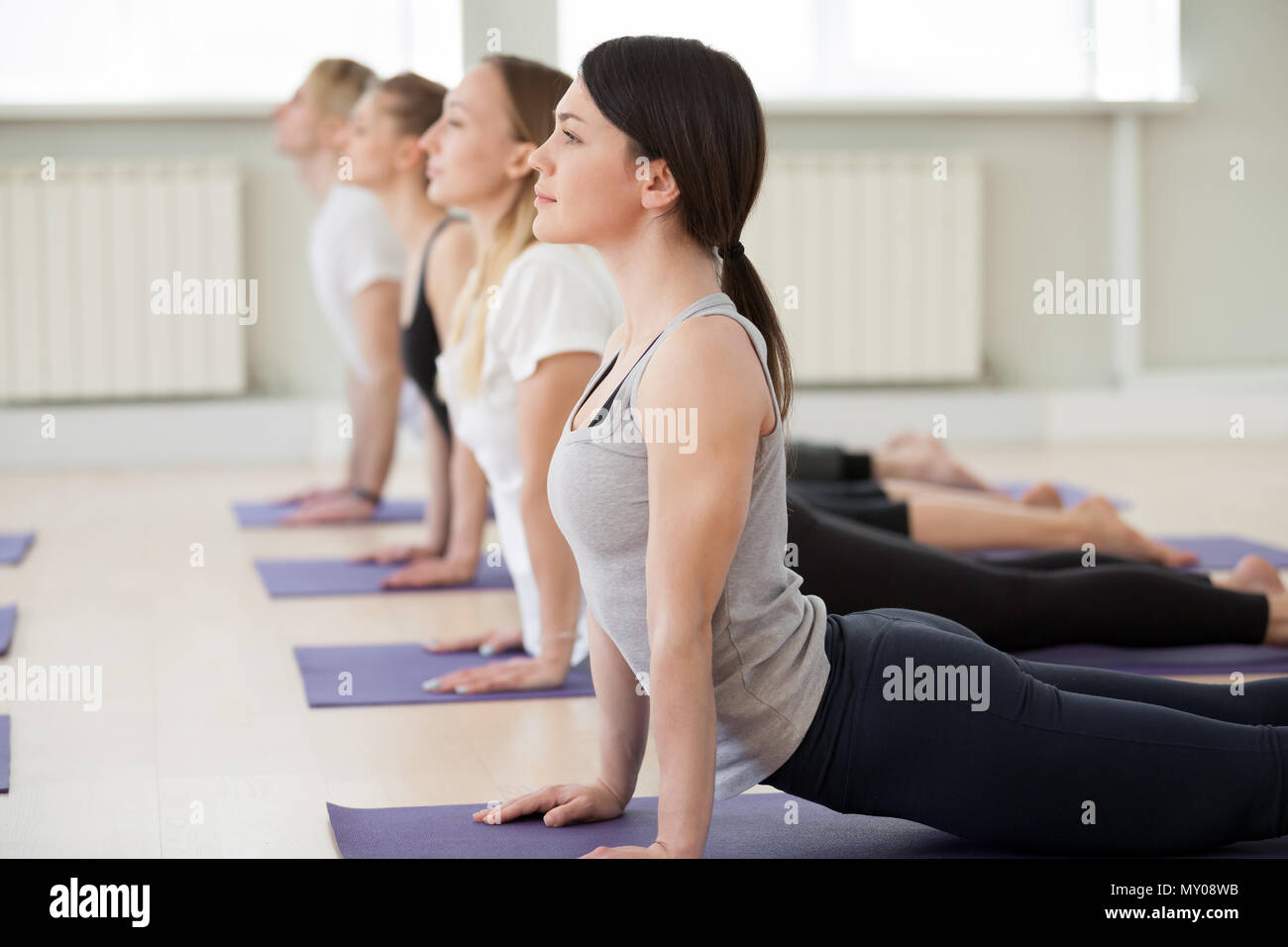 Group of young sporty people doing yoga, up facing dog exercise, Urdhva mukha shvanasana pose, indoor close up, yogi students working out in sport clu Stock Photo