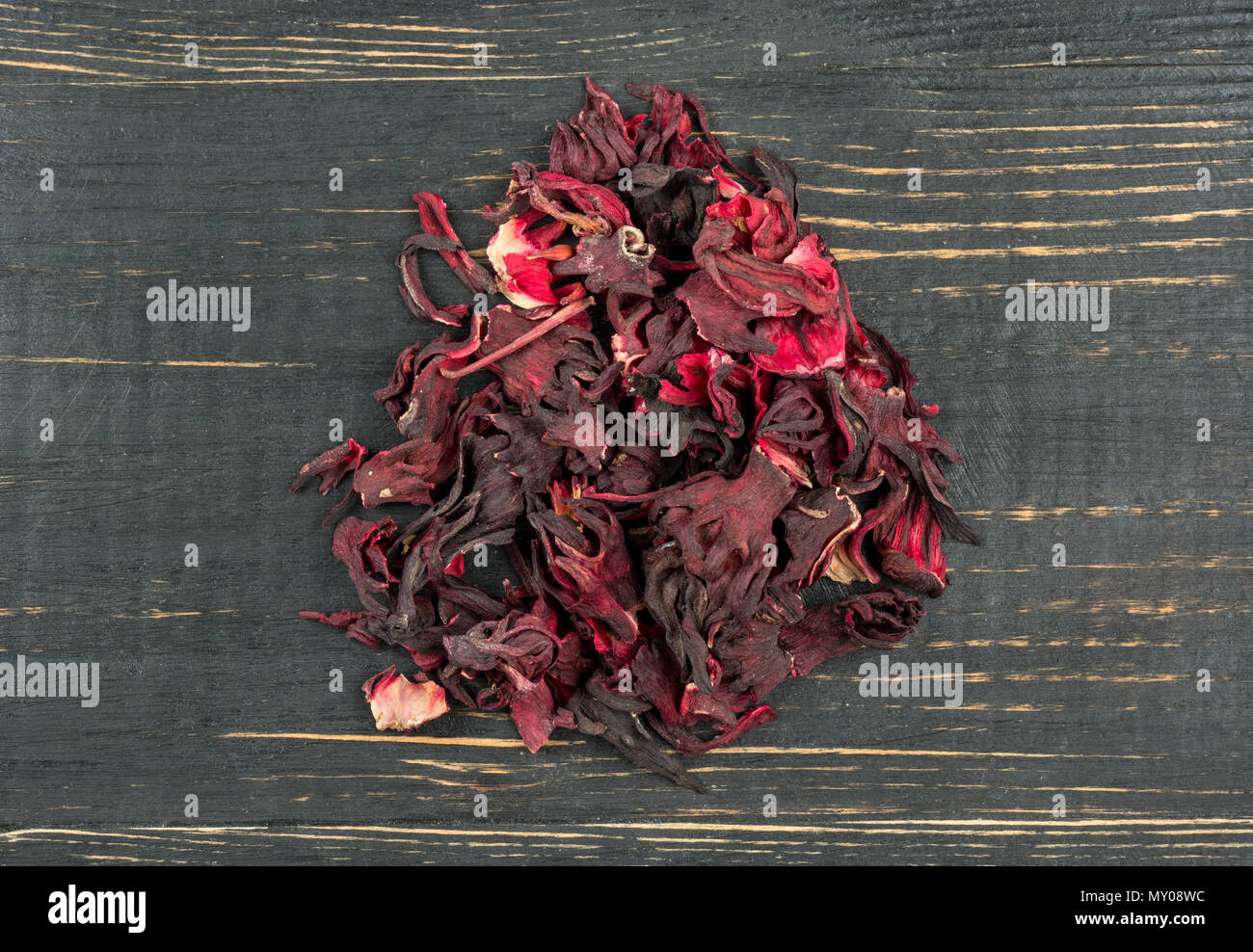 Heap of dry tea hibiscus on wooden background, top view - Stock Image