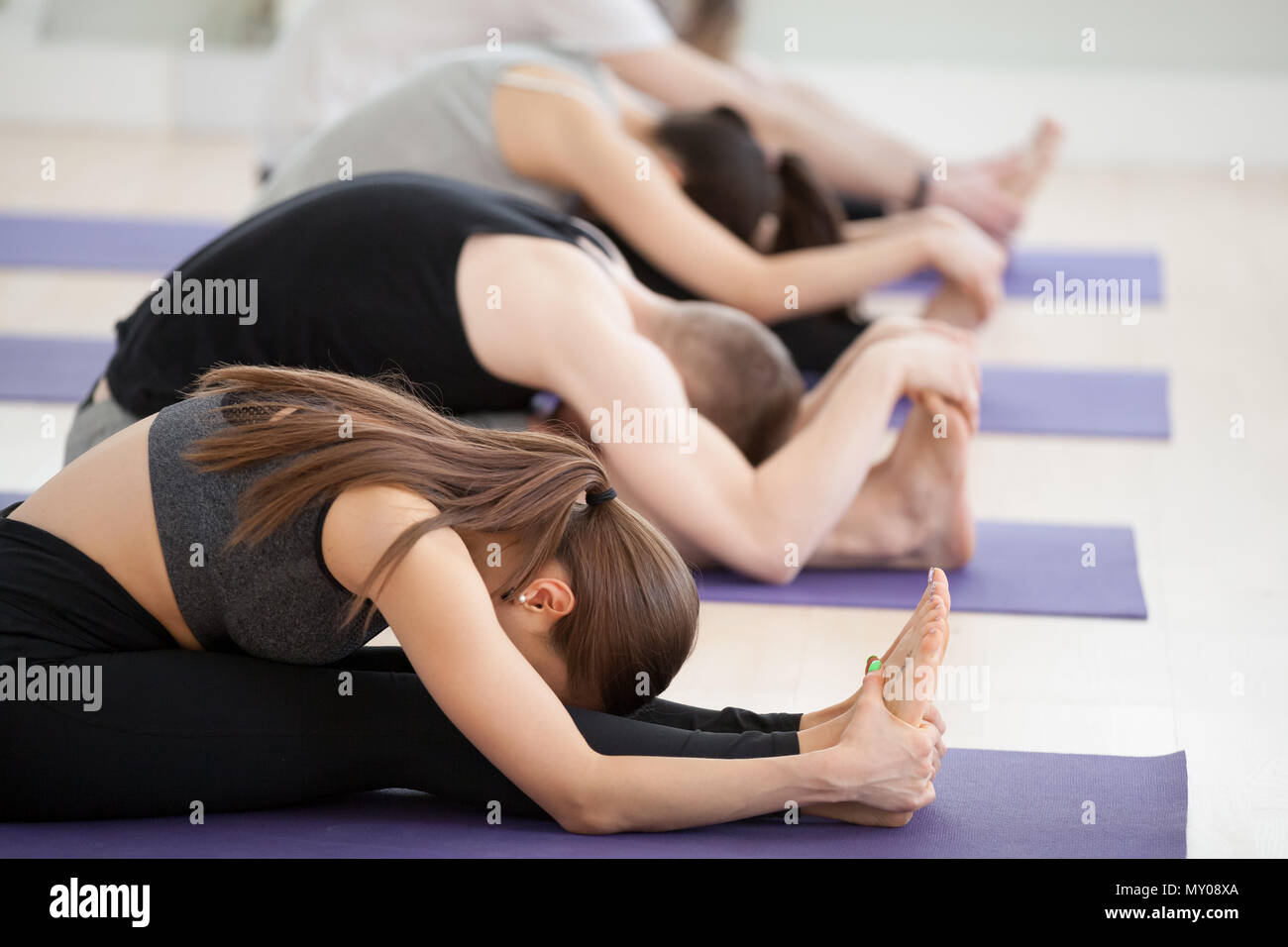 Group of young sporty people practicing yoga lesson, doing Seated forward bend exercise, paschimottanasana pose, indoor close up, yogi students workin Stock Photo