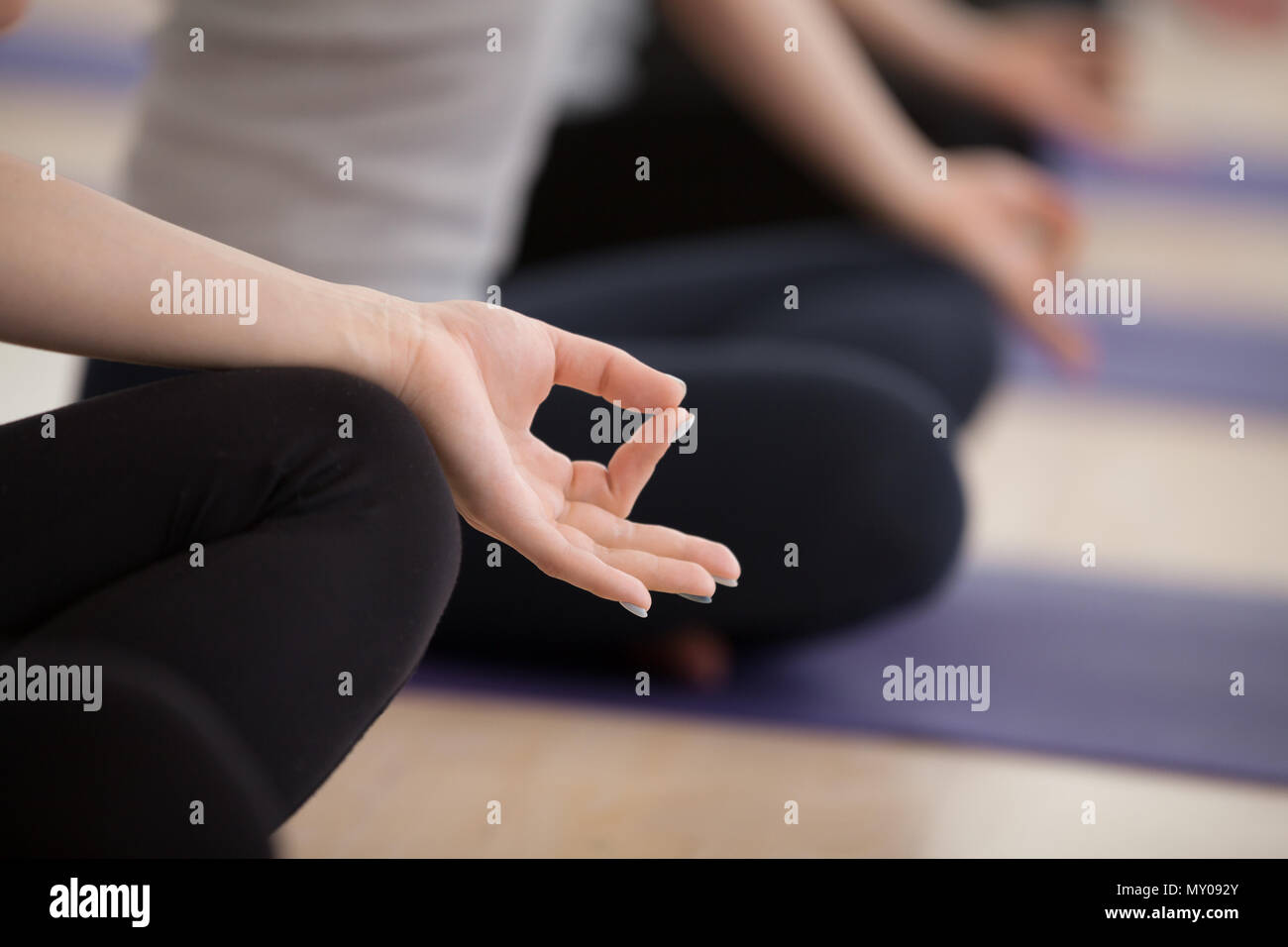 Sporty people practicing yoga lesson, sitting in Sukhasana exercise, Easy Seat pose, working out, indoor close up focus on mudra, studio. Mindful life Stock Photo