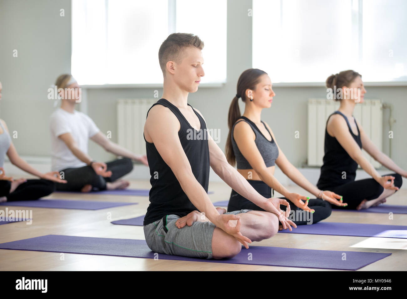 Group of young sporty people doing yoga in gym, Sukhasana exercise, Easy Seat pose, working out, indoor full length, students training in sport club,  Stock Photo