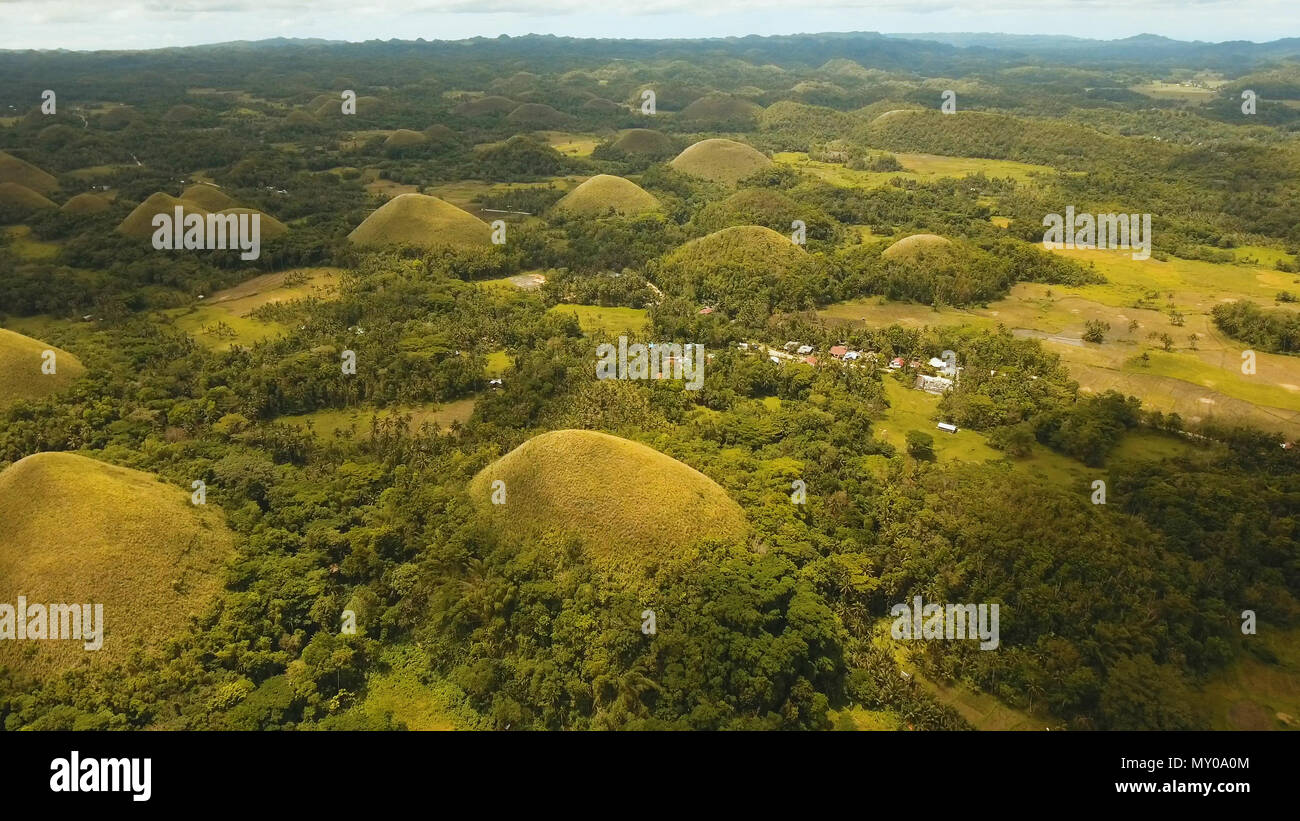 Amazingly shaped Chocolate hills on sunny day on Bohol island, Philippines. Aerial view Chocolate Hills in Bohol, Philippines are earth mounds scattered all over the town of Carmen. Travel concept. - Stock Image
