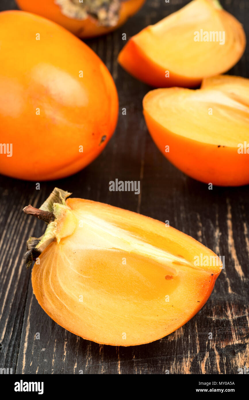 Fresh persimmon fruit with slice and half on wooden background - Stock Image