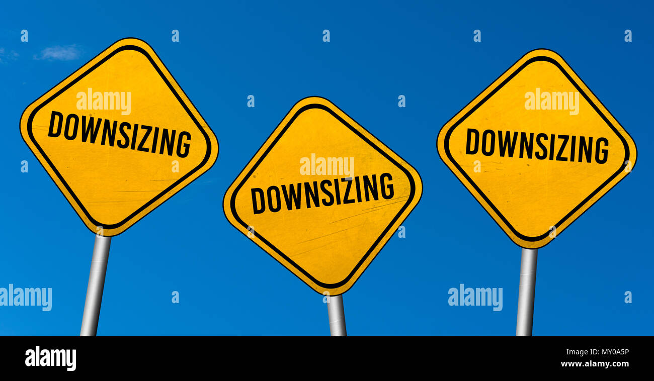 Downsizing - yellow signs with blue sky - Stock Image
